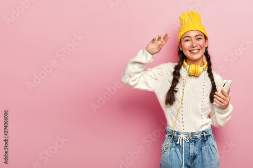 Horizontal shot of attractive mixed rcae woman holds modern cellphone, dances to favourite music, wears headphones around neck, poses against pink background, copy space area for your promotion - 294066006