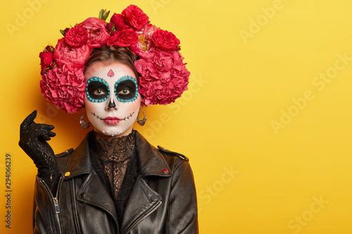 Poster Ecole de Danse Photo of young woman has face arfully painted to resemble skulls, wears black leather jacket and gloves, wears garland made of red aromatic flowers, supports spiritual journey of dead people