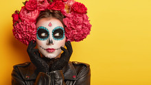 Horizontal Shot Of Thoughtful Female With Halloween Creative Makeup, Looks Away, Has Spooky Look, Wears Red Flower Wreath, Blank Space On Yellow Background. Woman Prepares For Mexican Day Of Dead