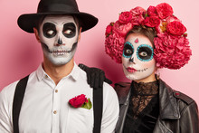 Shocked Couple Have Scary Face Expressions, Funky Makeup And Costumes, Wear Black And White Attire Decorated With Red Flowers, Dressed In Vampire Costumes, Pose Together In Studio Against Pink Wall