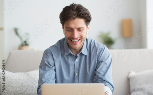 Photographie  Guy In Wireless Earphones Using Laptop Sitting On Couch Indoor