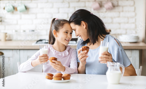 Photo Mother and daughter having a bite in kitchen