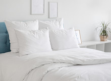 White Pillows And Duvet On The Blue Bed. White Pillows, Duvet And Duvet Case On A Blue Bed. White Bed Linen On A Blue Sofa. Bedroom With Bed And Bedding And Poster Frame Mock Up On The Wall.Front View