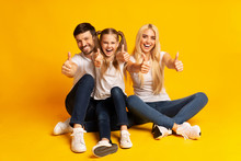 Family Gesturing Thumbs Up Sitting On Floor, Yellow Background