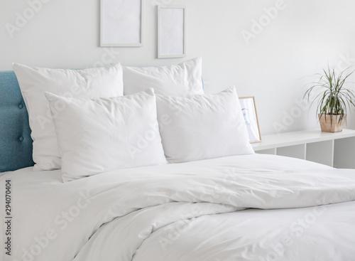 Obraz na plátně White pillows and duvet on the blue bed
