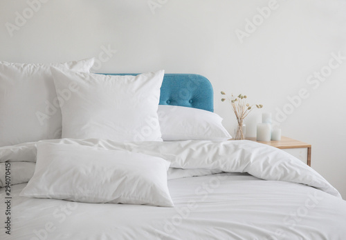 Fényképezés White pillows and duvet on the blue bed