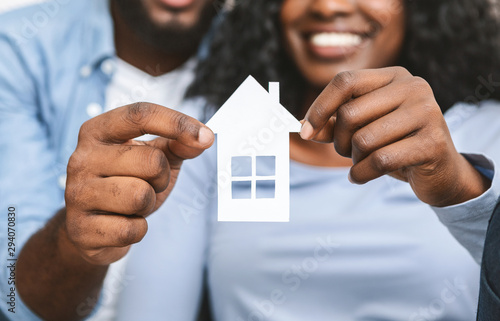 Close up of african couple holding wooden house - fototapety na wymiar