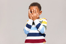 Frightened Dark Skinned Little Boy Covering Face With Both Hands As If Being Afraid To See Something Scary, Spying Through Hole Between Fingers. Shy African Child Hiding, Or Playing Hide And Seek