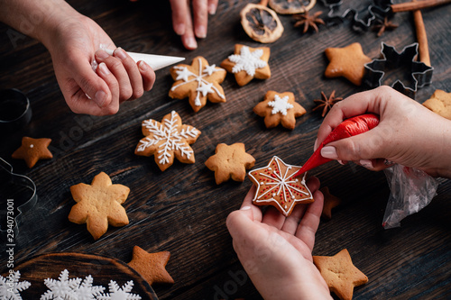 Fototapeta Christmas and New Year holidays, family weekend activities, celebration atmosphere. Friends decorating traditional gingerbread cookies obraz
