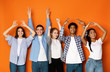 canvas print picture - Young friends gesturing with hands over orange background