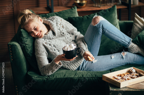 Obraz Christmas, cold autumn or winter day. Warming mood. Cheerful woman enjoy stayng at home drinking warm cocoa with marshmallows. Lazy weekend in knitted sweater on the couch. Cozy scene, hygge concept - fototapety do salonu