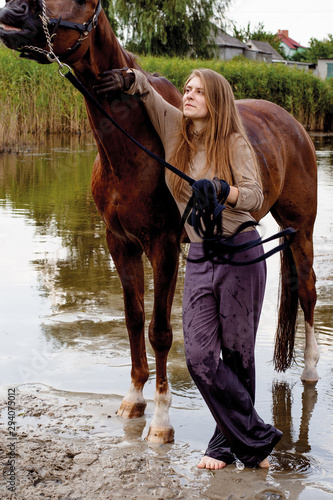 Valokuva photo young beautiful horsewoman walking a horse in a pond