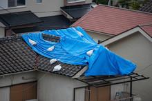 Tattered Blue Tarp On Roof Aft...