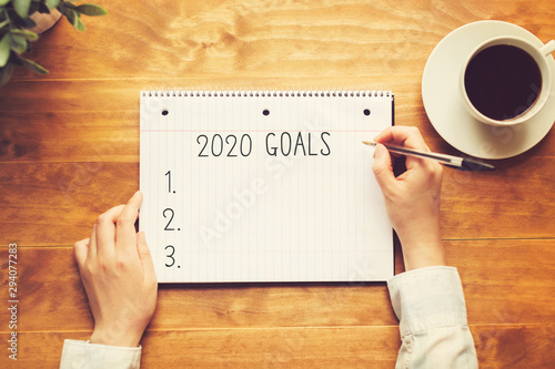 Fototapeta 2020 goals with a person holding a pen on a wooden desk obraz