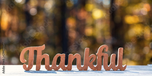 Thankful message in wooden letters Thanksgiving theme on a fall forest background
