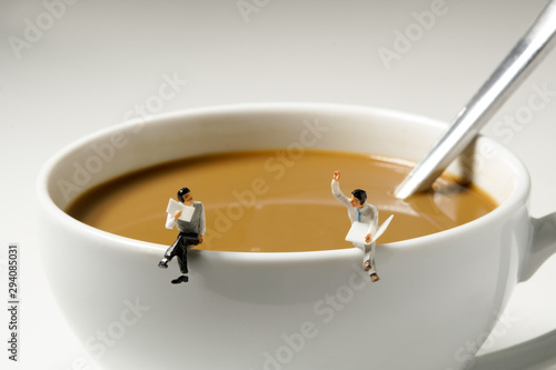 business miniature man sitting on white coffee cup edge