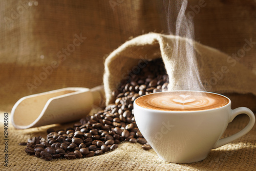 white coffee cup with hot steam smoke and roasted coffee beans around