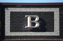 Raise Letter B On A Brick Wall Framed With Paint