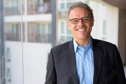 Fotografia  Happy mature Hispanic businessman smiling by the glass window of office building