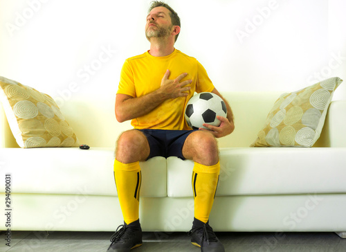Photo funny portrait of young man in football team uniform watching soccer game on TV