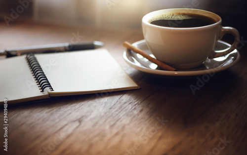Closeup black coffee in cup with open blank notebook on wooden table. Vintage light and dark tone - 294094849