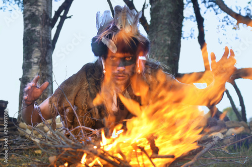 Obraz na plátně  evil sorcerer with the painted face that casts a spell over the campfire
