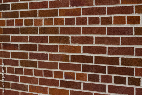 Vintage traditional red brown brick wall texture with common bond brickwork pattern (angle view)