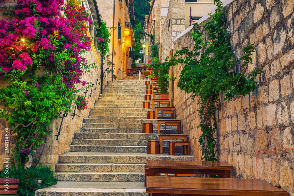 Fototapeta Narrow street and street cafe decorated with flowers, Hvar, Croatia