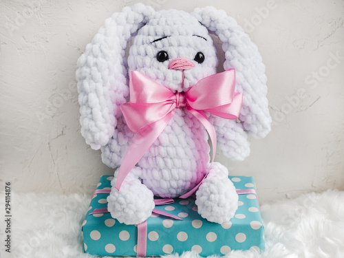 Beautiful, bright plush toy, white plaid and a gift box tied with a ribbon. Isolated background. Studio photo. Close-up, indoor. Day light