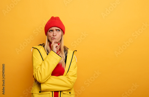 obraz lub plakat Girl thinks about something. Confused and pensive expression. Yellow background