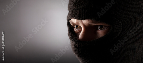angry man in a balaclava on a dark background. Fototapet