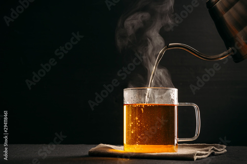 Tuinposter Thee The process of brewing tea, pouring hot water from the kettle into the Cup, steam coming out of the mug, water droplets on the glass, black background