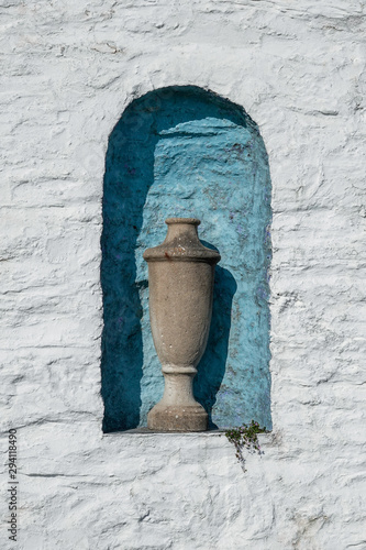 Italian style stone urn sitting in a blue alcove, with white wall surround Canvas Print