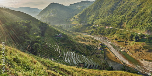 Fotobehang Rijstvelden Beautiful sunset landscape with small houses on hillside with rice terraces after rice harvesting, on the banks of a mountain river, between the villages of Ta Van and Sa Pa, in the north of Vietnam.