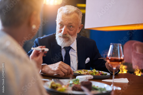 Senior caucasian bearded male sits and look at woman in restaurant in hotel Poster Mural XXL