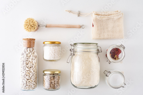 Fotografia Glass jars with food ingredients on a white background, top view