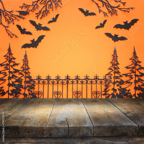 Fototapety, obrazy: holidays concept of Halloween. Empty rustic table in front of haunted alley with trees and bats over orange background. Ready for product display montage