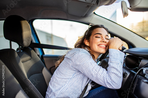 Young Woman Embracing Her New Car. Excited young woman and her new car indoors. Young and cheerful woman enjoying new car hugging steering wheel sitting inside - 294129235