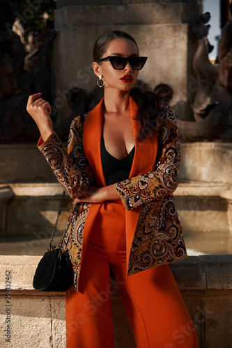 Fashion style outdoor portrait. Elegant woman in colorful orange suit with black handbag standing and posing against fountain in old town on a sunny evening, Sunny evening. Tropical city