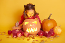Indoor Shot Of Little Cute Baby Sitting Isolated Over Yellow Studio Background, Halloween Fall Pumpkins, Apples And Leaves Around Child, Kid Looks Exited Into Glowing Vegetable, Last October Night.