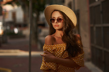 Closeup Outdoor Portrait Of Young Beautiful Caucasian Young Woman With Long Brunette Hair Wearing Yellow Polka Dot Dress, Sunglasses And Thatch Hat. Summer Sunny Evening Street