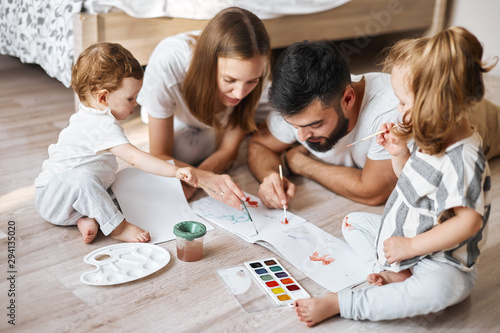 Fotografiet  young parents studing with children , developing their painting skills, close up