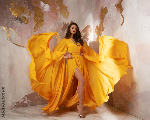 Valokuvatapetti Young beautful caucasian woman with long wavy brunette hair in yellow flying dress posing against wall