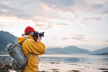 Hipster Traveler Photographer Takes A Photo Beautiful Nordic Landscape On Professional Camera. Man Tourist With Backpack Shoots A Photo Scandinavia Nature