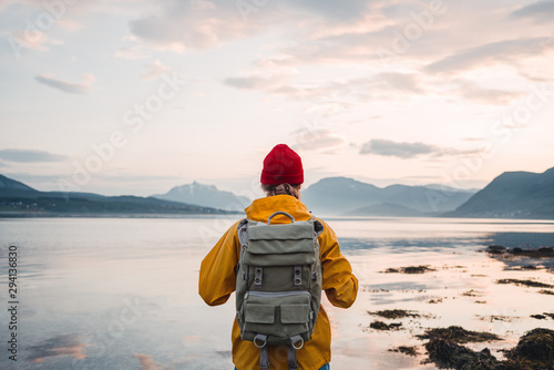 Fototapeta Back view of male tourist with rucksack standing on coast in front of great mountain massif while journey.  Man traveler wearing yellow jacket with backpack explore nature. Wanderlust lifestyle obraz