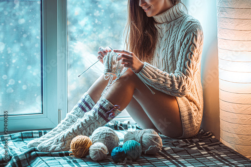 Cozy woman in knitted winter socks and white warm sweater enjoys knitting on a w Tableau sur Toile