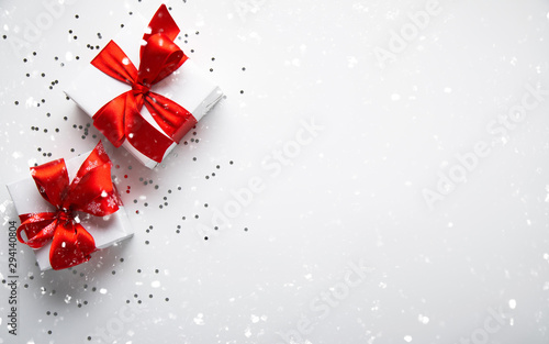 Fototapeta Merry Christmas and Happy Holidays greeting card. New Year. Valentine's day. White gifts with red ribbon, present on white background top view.	 obraz na płótnie