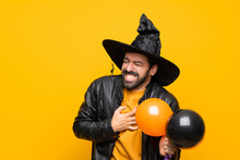 Man With Witch Hat Holding Black And Orange Air Balloons For Halloween Party Having A Pain In The Heart
