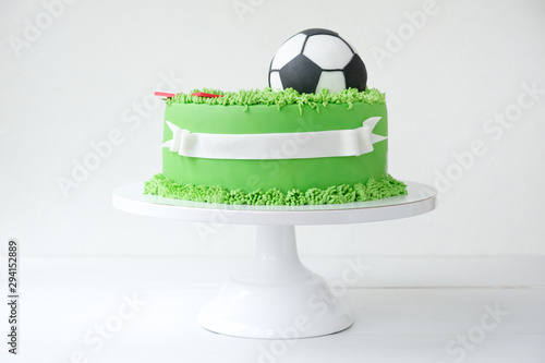 Cake on a football theme decorated with green grass and soccer ball on white background Wallpaper Mural