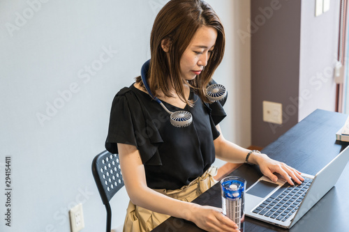 Photo ハンズフリー扇風機を使う女性